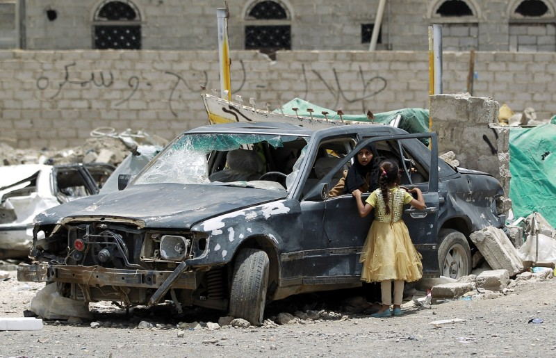 A Yemeni woman inpect a damaged car in a residential area that was destroyed by Saudi-led air strike last month, in the capital Sanaa, on May 18, 2015. Saudi-led coalition warplanes resumed strikes on rebel positions in southern Yemen after a five-day ceasefire expired, jeopardising efforts to deliver desperately needed aid. AFP PHOTO / MOHAMMED HUWAIS        (Photo credit should read MOHAMMED HUWAIS/AFP/Getty Images)