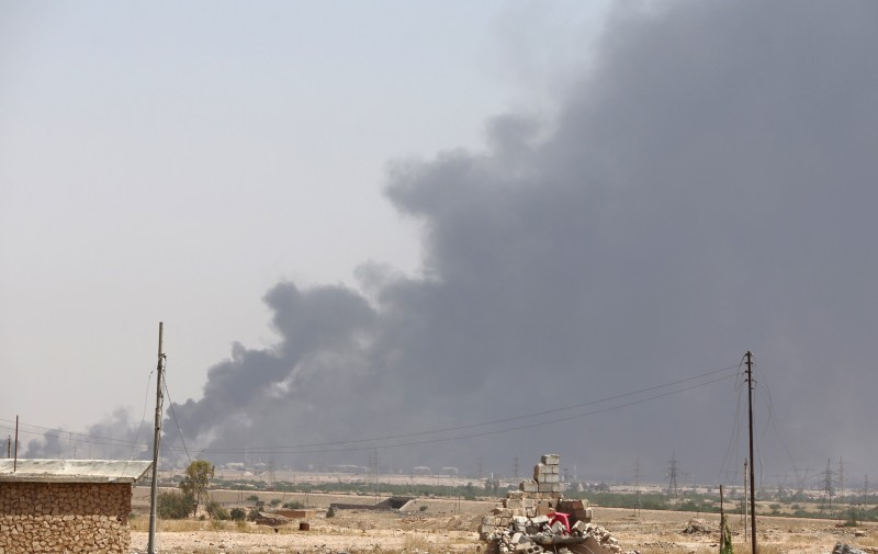 Smoke billows in the outskirts of Baiji refinery north of Tikrit, in the Salahaddin province, as the Iraqi army and Shiite popular mobilisation unit fighters conduct a joint operation to retake the remaining area of the oil refinery from Islamic State (IS) group jihadists, on May 25, 2015. Iraq rejected accusations by the US defence chief that its security forces dodged battle in Ramadi and lack the will to fight the IS group. AFP PHOTO / AHMAD AL-RUBAYE        (Photo credit should read AHMAD AL-RUBAYE/AFP/Getty Images)