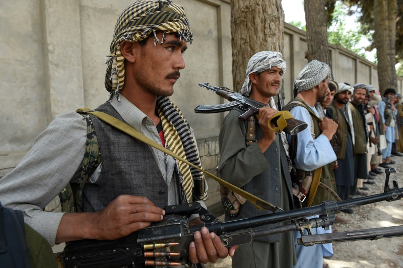 "TO GO WITH Afghanistan-unrest-militias,FOCUS by Anuj Chopra This photograph taken on May 23, 2015, shows Afghan militia forces as they stand with their weapons in Kunduz. The commander known as Pakhsaparan, or the ""wall breaker"", barked out commands at his bandolier-draped fighters, part of a patchwork of anti-Taliban militias in northern Afghanistan seeking to augment hard-pressed Afghan forces in a strategy fraught with risk. AFP PHOTO / SHAH Marai        (Photo credit should read SHAH MARAI/AFP/Getty Images)"