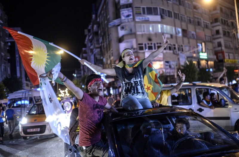 Young supporters of pro-Kurdish Peoples' Democratic Party (HDP) hold Kurdish flags as they celebrate the results of the legislative election, in Diyarbakir on June 7, 2015. The HDP easily surpassed the 10 percent barrier needed to send MPs to parliament. Under Turkey's proportional representation system, this means the Turkey's Islamic-rooted Justice and Development Party (AKP) will need to form a coalition for the first time since it first came to power in 2002. AFP PHOTO / BULENT KILIC        (Photo credit should read BULENT KILIC/AFP/Getty Images)