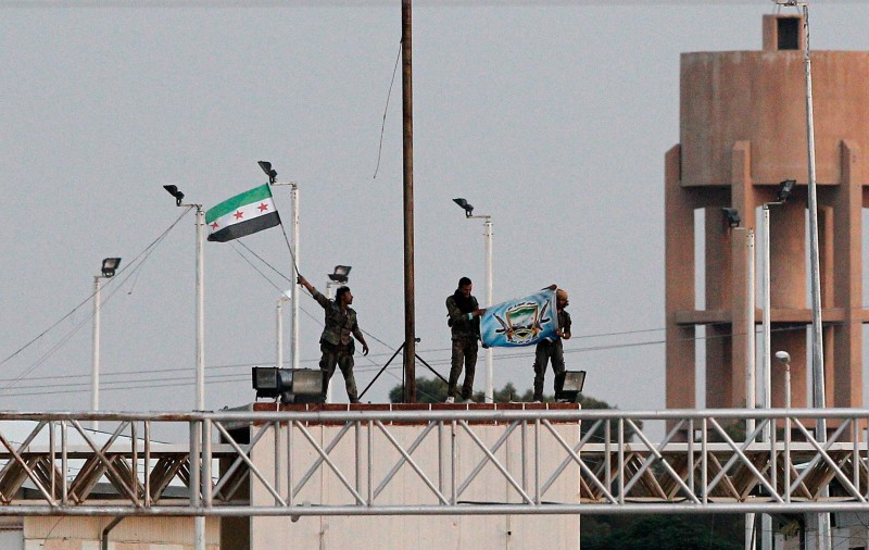 SANLIURFA, TURKEY - JUNE 15: Free Syrian Army fighters wave their flag as in the northern Syrian town of Tel Abyad as they are pictured from the Turkish border town of Akcakale, in Sanliurfa province, Turkey, June 15, 2015. Members of the Syrian Kurdish YPG militia took positions on the outskirts of the Islamic State stronghold of Tel Abyad. Thousands of Syrians cut through a border fence and crossed over into Turkey on Sunday, fleeing intense fighting in northern Syria between Kurdish fighters and jihadis.According to Turkish security officials 10,000 people to come across from Syria in last two days. (Photo by Gokhan Sahin/Getty Images)