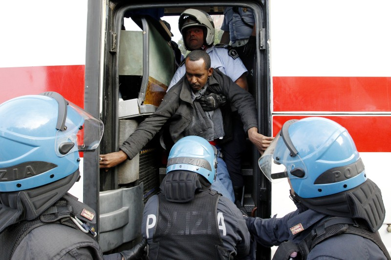 "Italian police officers attempt to force a migrant into an Italian Red-Cross vehicle at the Italian-French border in the Italian city of Ventimiglia on June, 16, 2015.  Italy and France engaged in a war of words as a standoff over hundreds of Africans offered a graphic illustration of Europe's migration crisis. Italian Interior Minister Angelino Alfano described images of migrants perched on rocks at the border town of Ventimiglia after being refused entry to France as a ""punch in the face for Europe.""  AFP PHOTO / JEAN CHRISTOPHE MAGNENET        (Photo credit should read JEAN CHRISTOPHE MAGNENET/AFP/Getty Images)"