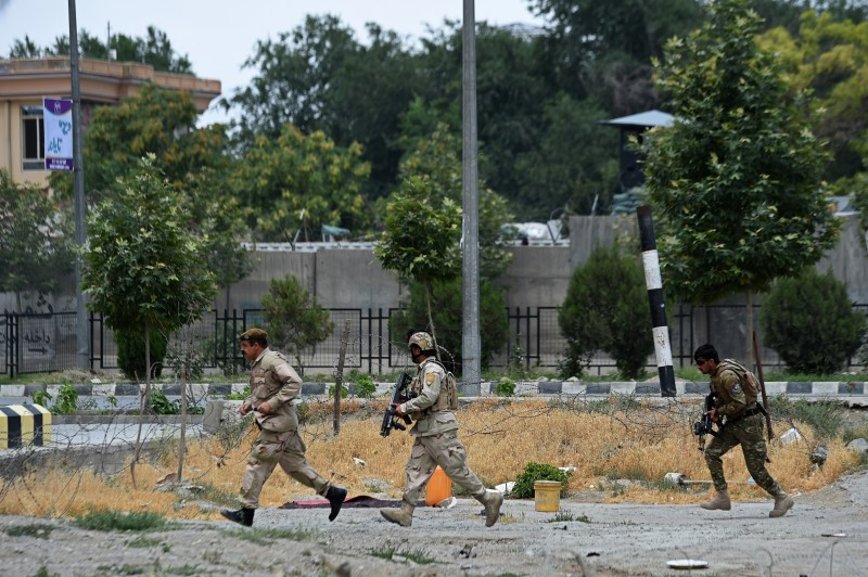 Afghan security personnel run at the scene of a suicide attack by Taliban militants on the Afghan parliament building in Kabul on June 22, 2015. Taliban militants attacked the Afghan parliament on June 22, with gunfire and explosions rocking the building, sending lawmakers running for cover in chaotic scenes relayed live on television.The insurgents tried to storm the complex after triggering a car bomb but were repelled and have taken position in a partially-constructed building nearby, officials said about the ongoing attack. All MPs were safely evacuated after the attack, which came as the Afghan president's nominee for the crucial post of defence minister was to be introduced in parliament. AFP PHOTO / Wakil Kohsar        (Photo credit should read WAKIL KOHSAR/AFP/Getty Images)