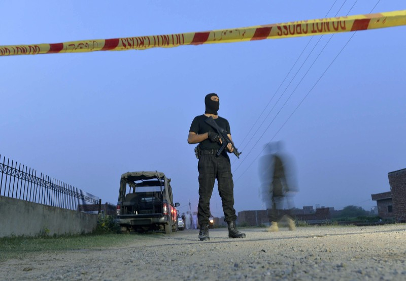 A Pakistani police commando stands alert at a cordon near a house on the outskirts of Lahore on June 29, 2015, following a raid on property allegedly used by Taliban militants.  Pakistani police and counter terrorism forces raided a house near the eastern city of Lahore and killed four Taliban militants, officials said. AFP PHOTO / ARIF ALI        (Photo credit should read Arif Ali/AFP/Getty Images)