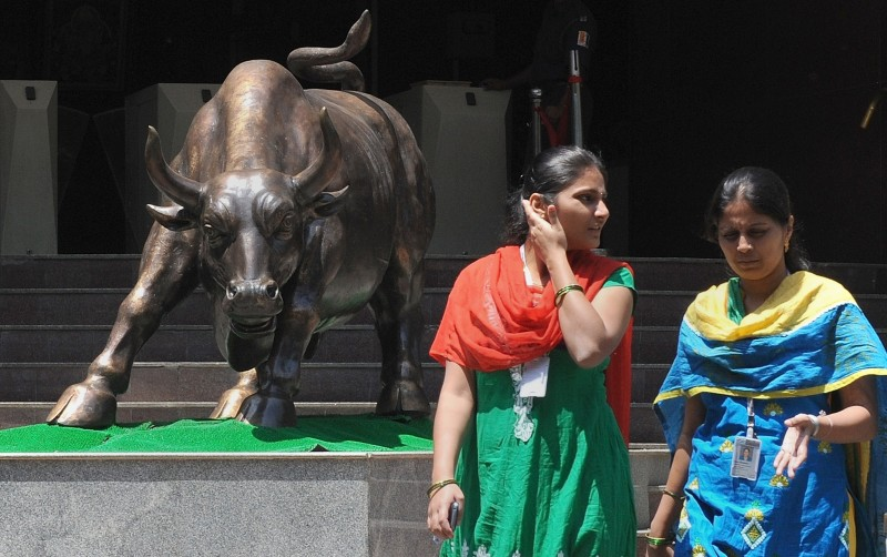 Indian office goers walk past the bronze bull outside the Bombay Stock Exchange (BSE) during intra-day trade in Mumbai on April 1, 2014. India's central bank kept key interest rates steady in a widely anticipated move less than a week before the start of national elections, due to start April 7. AFP PHOTO / INDRANIL MUKHERJEE        (Photo credit should read INDRANIL MUKHERJEE/AFP/Getty Images)