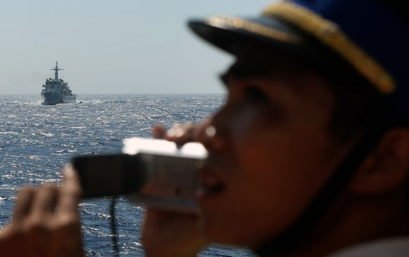 This picture taken from a Vietnam Coast Guard ship on May 14, 2014 shows a Vietnamese Coast Guard officer taking picture of a  China Coast Guard ship moving toward the Vietnamese ship near to the site of a Chinese drilling oil rig (R, background) being installed at the disputed water in the South China Sea off Vietnam's central coast. Vietnam National Assembly's deputies gathered for their summer session are discussing the escalating tension with China over the South China Sea's contested water. AFP PHOTO/HOANG DINH Nam        (Photo credit should read HOANG DINH NAM/AFP/Getty Images)