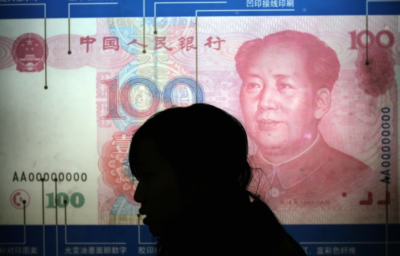 "Beijing, CHINA: A woman walks pass the Chinese renminbi 100 yuan note display at a museum in Beijing 01 March 2007.  Treasury Secretary Henry Paulson said the US remains ""dissatisfied"" with China's currency policies but argued for more open trade, instead of new barriers, to resolve the problem, as the former Goldman Sachs chief executive heads to Beijing next week for his third trip to China since he became Treasury secretary in July.     AFP PHOTO/GOH CHAI HIN (Photo credit should read GOH CHAI HIN/AFP/Getty Images)"