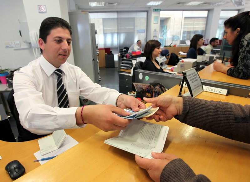 epa03644228 A Laiki Bank clerk hands out money at his bank's branch in Nicosia, Cyprus, 29 March 2013. Banks across Cyprus returned to normal opening hours on 29 March after the government enforced strict capital controls to save the country from a bank run. The measures, which include a daily withdrawal limit of 300 euros, a ban on cashing cheques and a 1,000 euro limit on money taken abroad by travelers, were implemented on 28 March after banks opened their doors for the first time in nearly two weeks.  EPA/KATIA CHRISTODOULOU