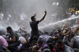 Protesters gesture as a riot police vehicle sprays a jet of water to disperse them during a rally against a recent decision to raise public electricity prices in Yerevan, Armenia, June 23, 2015. The protest started on Monday, when about 5,000 demonstrators marched to the presidential headquarters, as they rallied against a recent decision to raise public electricity prices, but were stopped by riot police. The protesters began a sit-in protest, blocking traffic on a central boulevard. Police asked demonstrators to leave the road but they refused. REUTERS/Vahram Baghdasaryan/Photolure     TPX IMAGES OF THE DAY       TEMPLATE OUT	     - RTX1HOHZ