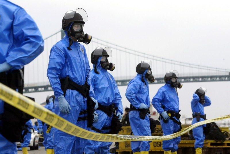 "LOS ANGELES - AUGUST 5:  Los Angeles police officers wearing contamination suits secure the area following the explosion of a ""dirty bomb"" during a simulated attack at a dock at the Port of Los Angeles on August 5, 2004 in Los Angeles, California. In the drill's scenario, a ""dirty bomb"" smuggled into the port in a shipping container exploded as a bus was driving by, releasing a plume of radioactivity. More than 850 civilian and military personnel representing more than 60 government agencies, community based and private-sector organizations are participating in the terror response drill, ""Determined Promise 2004"".       (Photo by David McNew/Getty Images)"
