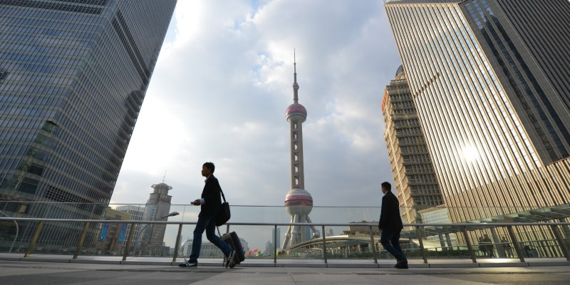 "TO GO WITH ""CHINA-US-DEBT,FOCUS"" BY BILL SAVADOVE Pedestrians walk through the financial district of Shanghai on October 16, 2013.  A US debt default could spur China to diversify its multi-trillion-dollar foreign exchange reserves, the world's largest, analysts say, as China seeks to boost its voice in the global economy. AFP PHOTO / Peter PARKS        (Photo credit should read PETER PARKS/AFP/Getty Images)"