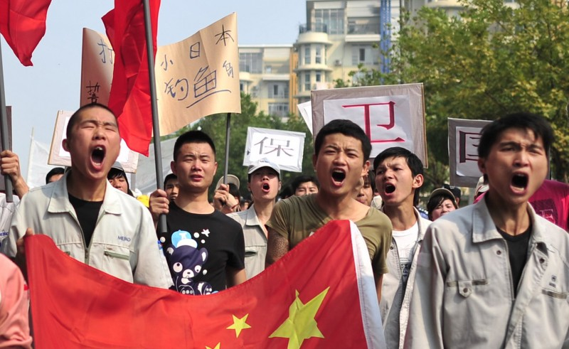 "Workers from Japanese company, Meiko Electronics (Wuhan) Limited, march with anti-Japan banners during a protest against Japan's ""nationalizing"" of Diaoyu Islands, also called Senkaku in Japan, in Wuhan, central China's Hubei province, on Septermber 18, 2012. Firms ranging from electronics giants Sony and Panasonic to Japan's three big carmakers -- Toyota, Honda and Nissan -- temporarily halted production at some or all of their China-based plants as anger erupted over a disputed island chain claimed by Tokyo and Beijing. CHINA OUT    AFP PHOTO        (Photo credit should read STR/AFP/GettyImages)"