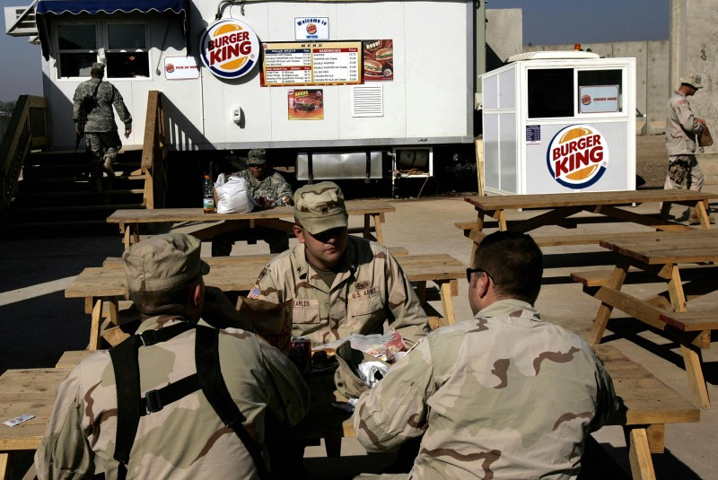 "TO GO WITH AFP STORY BY HARO CHAKMAKJIAN (FILES) -- File picture dated December 8, 2005 shows US Soldiers having lunch at ""Burger King"" at their military base in southern Baghdad. For a growing number of young US troops in Iraq, boredom is becoming the new enemy as major anti-insurgency raids turn rarer and their disengagement from the country starts to take shape.    AFP PHOTO/SAMUEL ARANDA (Photo credit should read SAMUEL ARANDA/AFP/Getty Images)"