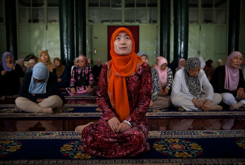 SANGPO, CHINA - JULY 11:  Hui Muslim female Imam Yonghua Zheng sits in front of worshippers as she prepares to lead prayer at the women's only Qingzhenshang Mosque on July 11, 2014 in Sangpo, Henan Province, China. As part of a tradition dating back to the late 19th century and unique to China's 10 million Hui Muslims, Zheng is one of hundreds of female Imams leading all female congregations in the women's only mosques of northwest China. Though able to teach and lead prayers for women, they are forbidden from overseeing funeral rituals or washing male corpses before burial.  (Photo by Kevin Frayer/Getty Images)