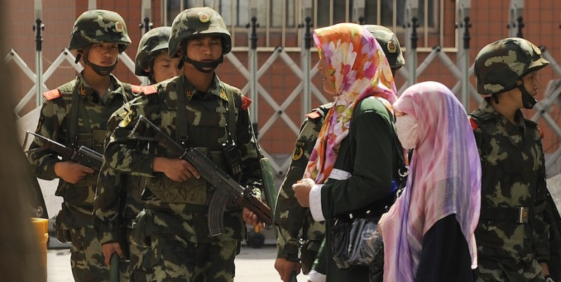 Muslim ethnic Uighur women pass a Chinese paramilatary police on patrol on a street in Urumqi, capital of China's Xinjiang region on July 3, 2010 ahead of the first anniversary of bloody violence that erupted between the region's Muslim ethnic Uighurs and members of China's majority Han ethnicity. The government says nearly 200 people were killed and about 1,700 injured in the unrest, China's worst ethnic violence in decades, with Han making up most of the victims.    AFP PHOTO/Peter PARKS (Photo credit should read PETER PARKS/AFP/Getty Images)