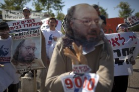 An Israeli youth demonstrator holds a picture and an effigy of Jonathan Pollard, a Jewish American who was jailed for life in 1987 on charges of spying on the United States, during a protest calling for his release in front of the American consulate in Jerusalem on July 11, 2011. Pollard is a convicted Israeli spy and a former United States Naval civilian intelligence analyst who received a life sentence in the mid 1980s. AFP PHOTO/MENAHEM KAHANA (Photo credit should read MENAHEM KAHANA/AFP/Getty Images)