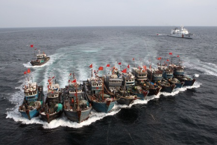 A picture taken on November 16, 2011 from a South Korean helicopter shows Chinese boats banded together with ropes, chased by a coastguard helicopter and rubber boats pacted with commandoes, after alleged illegal fishing in South Korean waters in the Yellow Sea off the southwestern coast county of Buan. South Korea's coastguard mobilised 12 ships, four helicopters and commandoes for a special three-day crackdown on illegal fishing by Chinese boats this week.  REPUBLIC OF KOREA OUT    AFP PHOTO/DONG-A ILBO (Photo credit should read DONG-A ILBO/AFP/Getty Images)