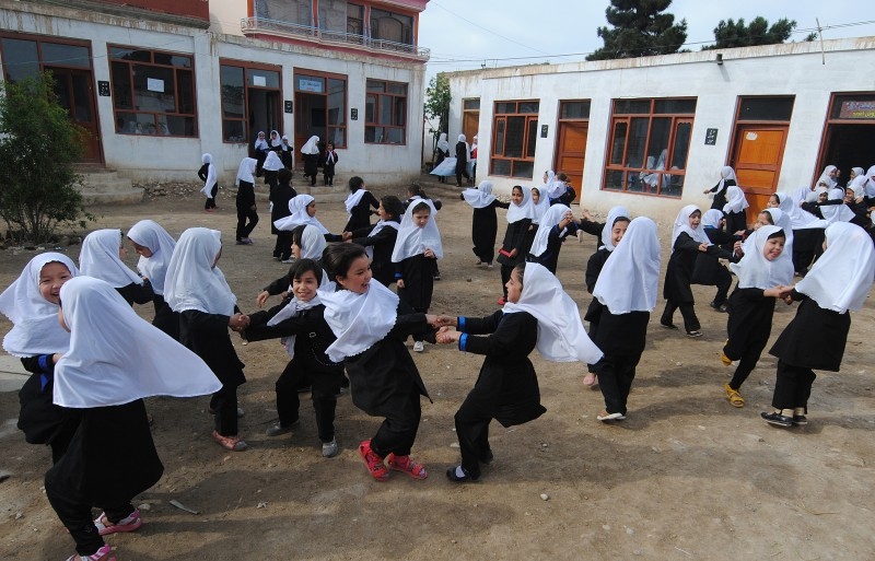 Afghan school girls play in the yard after their class at Ayesha primary school in Mazar-i Sharif on April 12, 2013. Under the hard line Taliban, who ruled Afghanistan between 1996 and 2001, cinema was banned and girls were prohibited from attending school.  AFP PHOTO/ Farshad USYAN        (Photo credit should read FARSHAD USYAN/AFP/Getty Images)