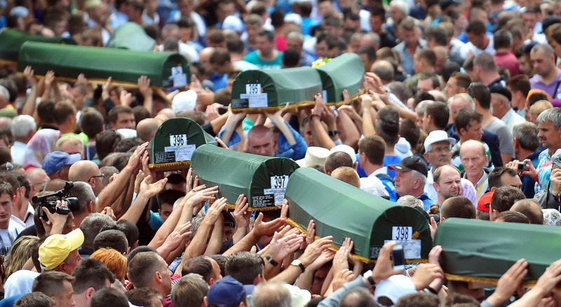 Bosnian Muslims carry body caskets of their relatives killed during Srebrenica 1995 massacre as they prepare for mass burial at a memorial cemetery in the village of Potocari near the eastern Bosnian town of Srebrenica on July 11, 2013. Bosnia buried 409 victims of the Srebrenica massacre on July 11, including a newborn baby, on the 18th anniversary of the worst slaughter in post-war Europe. More than 15,000 people travelled to Potocari, near Srebrenica to attend the mass funeral of victims whose remains were found in mass graves and only identified almost two decades after the 1995 killing.  AFP PHOTO / ELVIS BARUKCIC        (Photo credit should read ELVIS BARUKCIC/AFP/Getty Images)