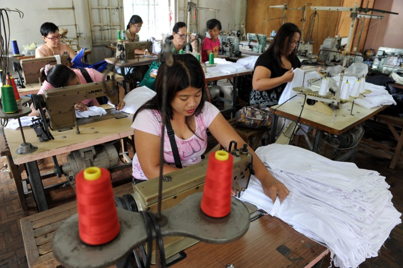 Women work at a sweatshop sewing clothes under contract with local clothing manufacturers in Manila, the Philippines, on July 12, 2013.