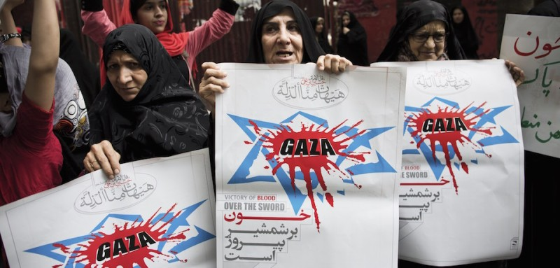 Iranian women hold up anti-Israel posters during a protest outside the United Nations offices in Tehran on July 15, 2014, held by a small group of demonstrators against Israel's deadly air offensive on the Gaza Strip this month. AFP PHOTO/BEHROUZ MEHRI        (Photo credit should read BEHROUZ MEHRI/AFP/Getty Images)