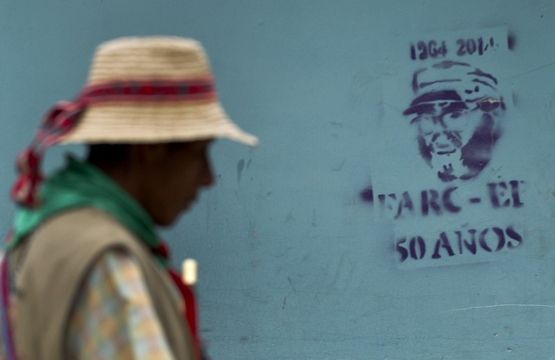 A Colombian indigenous walks next to a graffiti of late FARC commander Alfonso Cano, in Toribio, department of Cauca, Colombia, on November 8, 2014. Seven suspected FARC guerrillas will be tried Sunday by an indigenous court for murdering two leaders of the Nasa tribe in western Colombia, officials said. When crimes are committed in aboriginal territory, the punishment for the accused is decided by the community and not the ordinary justice system. The suspected Revolutionary Armed Forces of Colombia (FARC) rebel fighters on Wednesday attacked two native leaders who were removing billboards praising the late leader of the Revolutionary Armed Forces of Colombia, Guillermo Leon Saenz, also known as Alfonso Cano. AFP PHOTO / LUIS ROBAYO        (Photo credit should read LUIS ROBAYO/AFP/Getty Images)