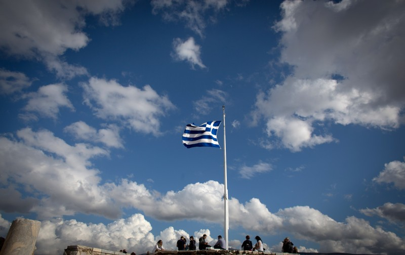 ATHENS, GREECE - JANUARY 26:  The Greek flag flies at the Acropolis following the electoral success by Syriza in the Greek general election yesterday on January 26, 2015 in Athens, Greece.  The radical left party Syriza won the snap Greek general election and has asked the right-wing Independent Greek party to form a anti-austerity coalition.  (Photo by Matt Cardy/Getty Images)