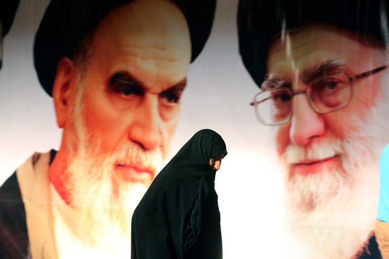 An Iranian woman walks past a giant poster showing supreme leader, Ayatollah Ali Khamenei (R) and the founder of Iran's Islamic Republic, Ayatollah Ruhollah Khomeini (L) during a ceremony marking the 36th anniversary of his return from exile on February 1, 2015 at Khomeini's mausoleum in a suburb of Tehran. Khomeini returned from exile in 1979, the trigger for a revolution which spawned an Islamic state now engulfed in a deep political crisis.  AFP PHOTO/ATTA KENARE        (Photo credit should read ATTA KENARE/AFP/Getty Images)