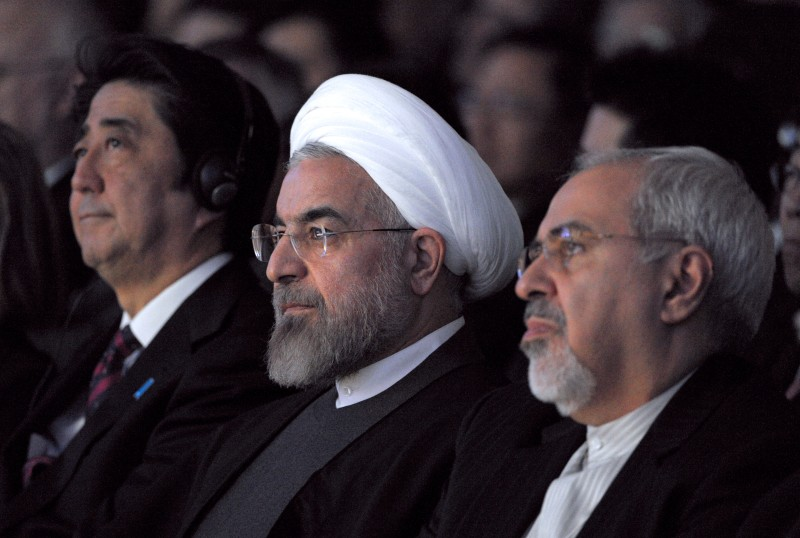 Iranian President Hassan Rouhani (C) sits next to Japanese Prime Minister Shinzo Abe (L) and Iranian Foreign Minister Mohammad Javad Zarif (R) during the World Economic Forum in Davos on January 22, 2014. Iran's President Hassan Rouhani takes centre stage at the Davos World Economic Forum Thursday, as he seeks to drum up investment for his sanctions-hit economy amid thawing relations with the West. AFP PHOTO ERIC PIERMONT        (Photo credit should read ERIC PIERMONT/AFP/Getty Images)