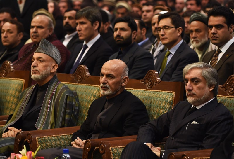 Afghan President Ashraf Ghani (C), Chief Executive Officer Abdullah Abdullah (R) and former president Hamid Karzai look on during a ceremony to mark the first anniversary of the death of former vice president Mohammad Qasim Fahim at the loya jirga hall in Kabul  on March 9, 2015. Former Afghan vice president Mohammad Qasim Fahim died of natural causes after a turbulent life that reflected the country's recent past. Fahim, a leader of the Tajik ethnic minority, was senior vice-president under President Hamid Karzai.  AFP PHOTO / SHAH Marai        (Photo credit should read SHAH MARAI/AFP/Getty Images)
