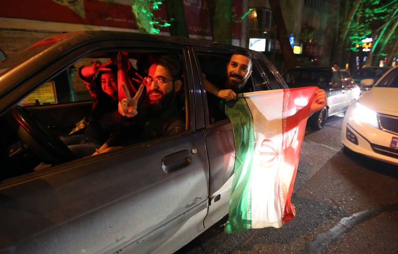 "People flash the ""V for Victory"" sign and hold an Iranian flag out of a car window as they celebrate on Valiasr street in northern Tehran on April 2, 2015, after the announcement of an agreement on Iran nuclear talks. Iran and global powers sealed a deal on April 2 on plans to curb Tehran's chances for getting a nuclear bomb, laying the ground for a new relationship between the Islamic republic and the West. AFP PHOTO / ATTA KENARE        (Photo credit should read ATTA KENARE/AFP/Getty Images)"