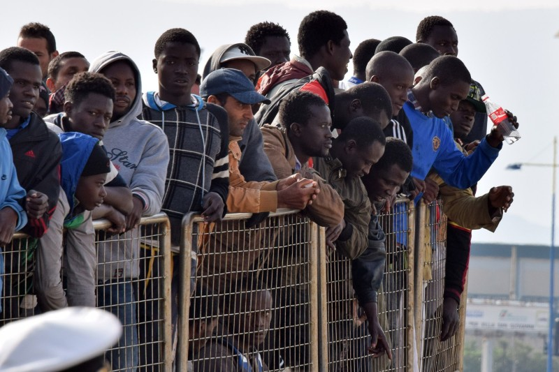 Migrants wait to disembark from a military ship following a rescue operation at sea as part of the Frontex-coordinated Operation Triton, on May 6, 2015 in Messina harbour. Italy's coastguard said it had rescued a total of 650 migrants yesterday and a total of over 1,700 were landed at various ports today as a consequence of what was one of the busiest weekends on record for rescues in the waters off Libya.  AFP PHOTO / GIOVANNI ISOLINO        (Photo credit should read GIOVANNI ISOLINO/AFP/Getty Images)