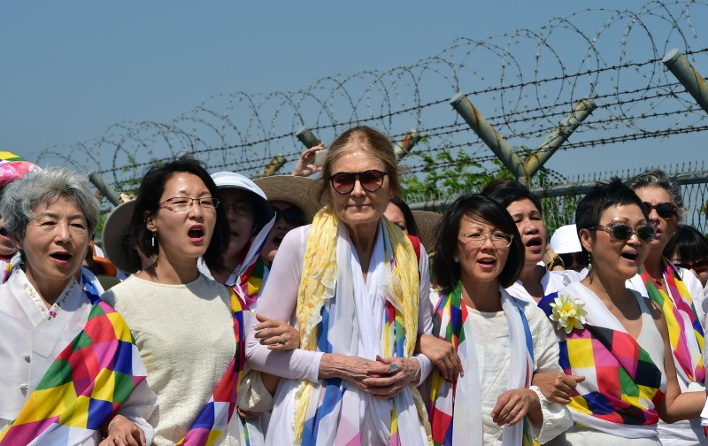 US feminist Gloria Steinem (C) and South Korean peace activists march along a military fence at a military check point in Paju on May 24, 2015 after she crossed the border line through the demilitarised zone (DMZ) separating the two Koreas.  An international group of women peace activists, led by American feminist Gloria Steinem, made a rare crossing on May 24 of one of the world's most militarised borders between North and South Korea. AFP PHOTO / JUNG YEON-JE        (Photo credit should read JUNG YEON-JE/AFP/Getty Images)