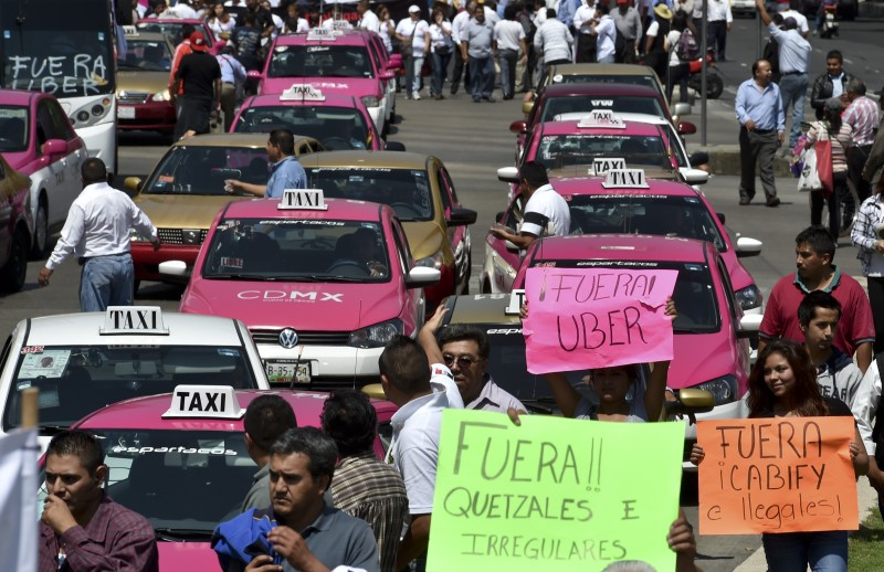 Taxi drivers take part in a protest against the private taxi company Uber for alleged unfair competition, in Mexico City on May 25, 2015. Thousands of taxi drivers protested across the Mexican capital to demand the government to take action against Uber, while the company retaliates by offering free transport in the city.   AFP PHOTO / Yuri CORTEZ        (Photo credit should read YURI CORTEZ/AFP/Getty Images)
