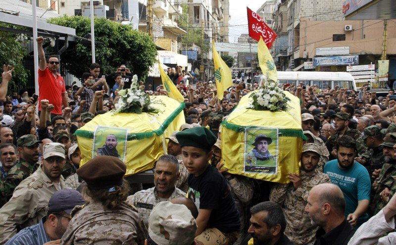 Fighters from Lebanon's Shiite movement Hezbollah carry the coffins of fellow militants, Ahmed Hareb (R) and Adel Hamidi during their funeral on June 6, 2015 in a southern suburb of the Lebanese capital Beirut after they were killed in combat alongside government forces in the Syria. AFP PHOTO / STR        (Photo credit should read -/AFP/Getty Images)
