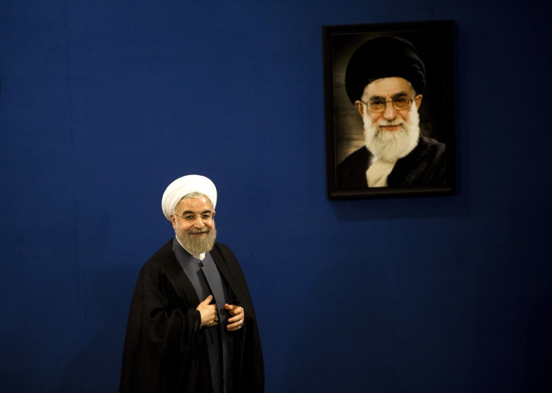 "Iranian President Hassan stands next to a portrait of supreme leader Ayatollah Ali Khamenei as he leaves at the end of a press conference in Tehran on June 13, 2015. There are still ""many differences over details"" of a nuclear deal Iran and world powers are trying to conclude by June 30, Rouhani said.  AFP PHOTO / BEHROUZ MEHRI        (Photo credit should read BEHROUZ MEHRI/AFP/Getty Images)"