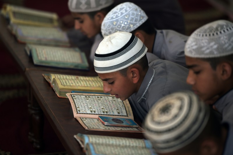 "TO GO WITH: Pakistan-Unrest-Education-Religion, FEATURE by Gohar ABBAS This photograph taken on May 5, 2015 shows Pakistani students of a madrassa or Islamic school recite the Quran at their seminary in Islamabad. Pakistan pledged to crack down on religious seminaries suspected of fostering extremism following a Taliban school massacre that left more than 130 children dead, but the move faces stiff resistance from conservatives. Amid a wave of outrage after the attack at the school in the northwestern city of Peshawar, the government announced a ""National Action Plan"" to fight back against the militants. AFP PHOTO/ Aamir QURESHI        (Photo credit should read AAMIR QURESHI/AFP/Getty Images)"