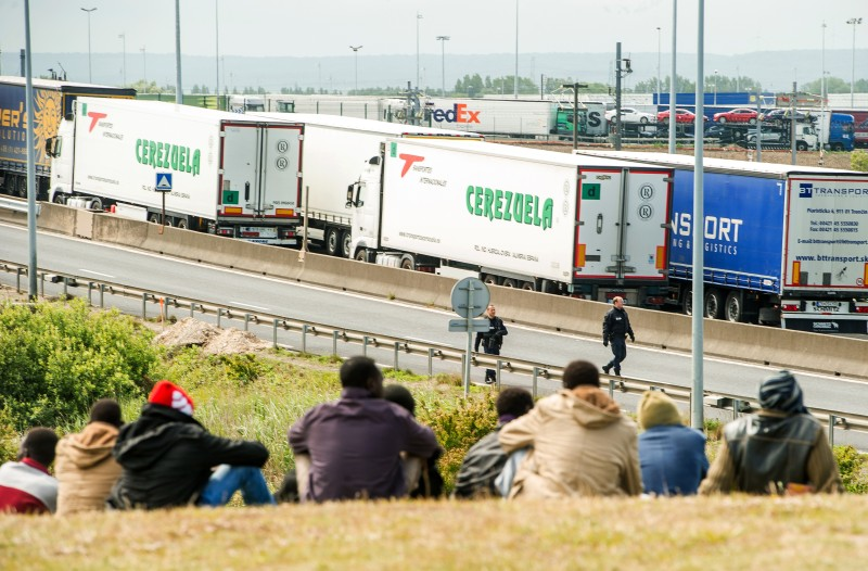 Migrants wait near the A16 highway as they try to access the Channel Tunnel on June 23, 2015 in Calais, northern France. AFP PHOTO PHILIPPE HUGUEN        (Photo credit should read PHILIPPE HUGUEN/AFP/Getty Images)