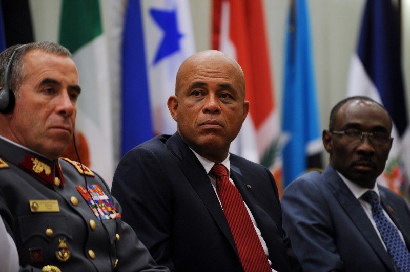 (L-R)  President of the Council of Delegates of the Inter-American Defense Board (IADB) Lieutenant General Araya Menghini, Chairman of the Council of Delegates of the Inter-American Defense Board, Haitian President, Michel Martelly, and Prime Minister  Evans Paul attend the official ceremony of presentation of the White Book about Security and National Defence for economic development  and sustainable social in Haiti, at the Oasis Hotel in Petion Ville, on June 25,2015. AFP PHOTO/HECTOR RETAMAL        (Photo credit should read HECTOR RETAMAL/AFP/Getty Images)
