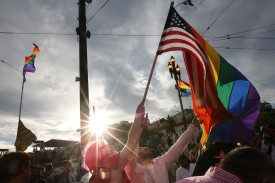 SAN FRANCISCO, CA - JUNE 27: A woman helps Francisco Pavon, center, wave a rainbow pride flag and an American flag during a gay pride celebration on June 27, 2015 in San Francisco, California.  The Supreme Court ruled that same-sex couples have a constitutional right to marry nationwide without regard to their state's laws. (Photo by Elijah Nouvelage/Getty Images)