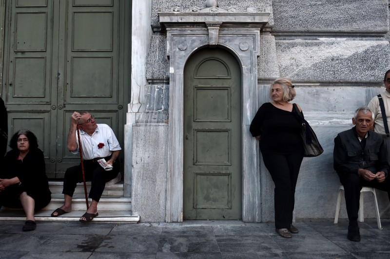 Pensioners wait outside a national Bank branch, as banks only opened for the retired to allow them to cash up to 120 euros in Athens on July 1, 2015. The European Union will decide whether to grant Greece a last-minute bailout package to avoid pushing it further towards an exit from the eurozone. Greece failed on the eve to make a 1.5 billion euro ($1.7 billion) payment to the International Monetary Fund, becoming the first industrialised country to do so.  AFP PHOTO / ARIS MESSINIS        (Photo credit should read ARIS MESSINIS/AFP/Getty Images)