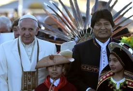 Pope Francis (L) greets Bolivian native children next to Bolivian President Evo Morales during a welcoming ceremony in El Alto, a plateau over La Paz, 4,000 meters above sea-level, on his first visit to Bolivia on July 8, 2015. Pope Francis, the first Latin American pontiff, arrived in Bolivia on the second leg of a three-nation tour of the continent's poorest countries, where he has been acclaimed by huge crowds.      AFP PHOTO / VINCENZO PINTO        (Photo credit should read VINCENZO PINTO/AFP/Getty Images)