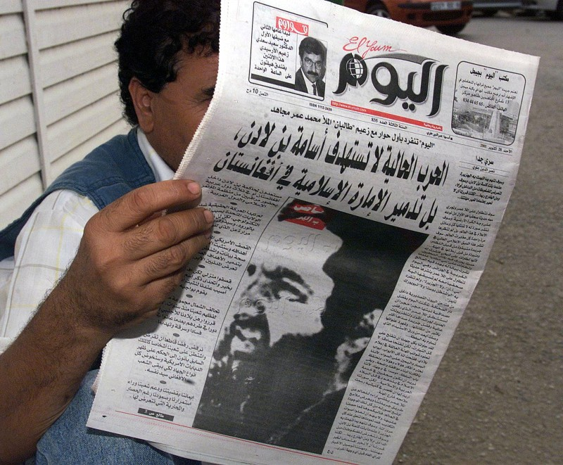 "ALGIERS, ALGERIA - OCTOBER 28:  A man reads 28 October 2001 in Algiers the Algerian daily El Youm, with on its frontpage a picture presented by the newspaper as a portrait of Mullah Mohammed Omar. The leader of Afghanistan's ruling Taliban regime Mullah Mohammed Omar said in an interview with El Youm that the ""real war"" against the United States has not yet begun, and promised to give the US a ""bitter lesson"". AFP PHOTO HOCINE  (Photo credit should read HOCINE/AFP/Getty Images)"