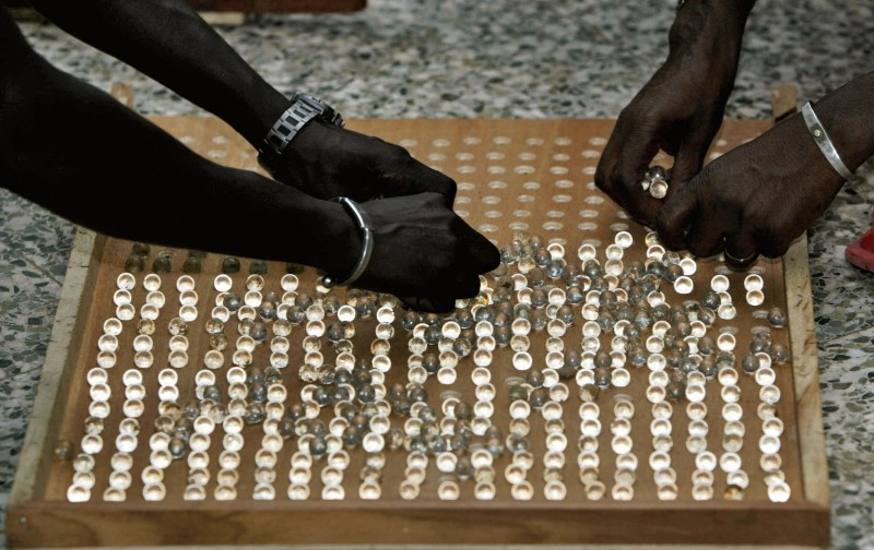 Bakau, GAMBIA:  Election officials set up marbles on a board to count the votes after the presidential elections in Bakau early 22 September 2006. Early results today showed Yahya Jammeh, who seized power in a coup 12 years ago, was on track to win a third term as president of mainland Africa's smallest country. Jammeh has won in 12 of the 48 voting regions to have reported provisional results from yesterday's presidential election, according to the results released by the commission over national television and radio.AFP PHOTO SEYLLOU  (Photo credit should read SEYLLOU/AFP/Getty Images)