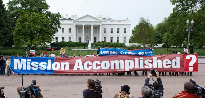 "Members of the ""The Iraq Campaign 2008"" hold a large replica of  ""Mission Accomplished"" banner on Pennsylvania Avenue in front of the White House in Washington, DC May 1, 2008, marking the fifth anniversary of President Bush's ""Mission Accomplished"" speech after landing on board a US aircraft carrier, proclaiming the end of major combat operations in Iraq.  AFP Photo/Paul J. Richards (Photo credit should read PAUL J. RICHARDS/AFP/Getty Images)"