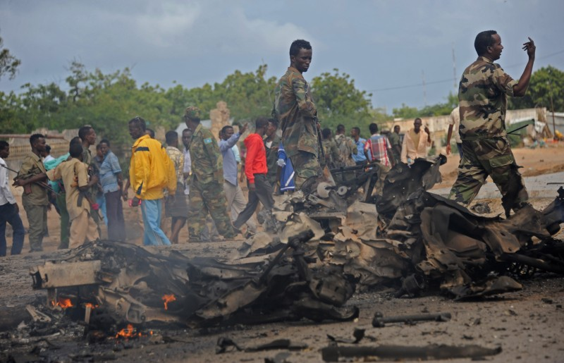 Soldiers patrol around the wreckage of a suicide car bomber that smashed into pickup  truck carrying security officers, on June 24, 2015 in Mogadishu, in the latest in a string of attacks.  There was no immediate claim of responsibility, but Somalia's Al-Qaeda linked Shebab carry out regular bombings and attacks in the troubled capital. AFP PHTO/MOHAMED ABDIWAHAB        (Photo credit should read Mohamed Abdiwahab/AFP/Getty Images)