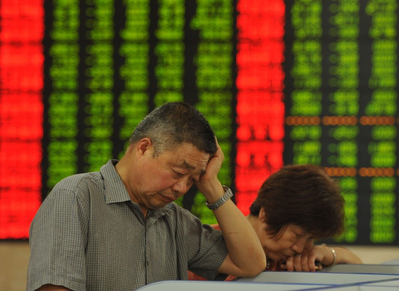 TO GO WITH China-economy-stocks, FOCUS by Fran Wang This photo taken on June 26, 2015 shows investors checking the share prices in a stock firm in Fuyang, east China's Anhui province. When China's main share index hit a seven-year high earlier this month, it topped off a run that had seen it more than double in value over the past year, placing it among the world's top performers. AFP PHOTO   CHINA OUT        (Photo credit should read STR/AFP/Getty Images)