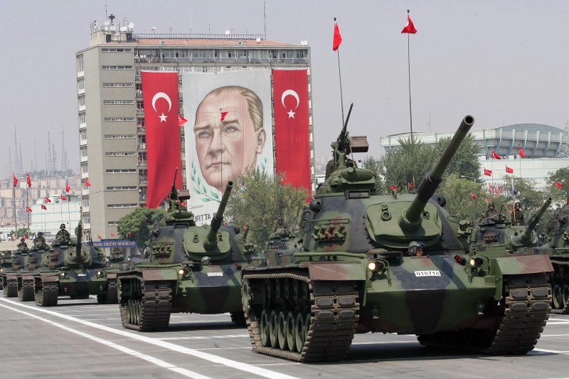 Turkish army tanks parade in front of a giant banner with a portrait of the founder of modern Turkey Mustafa Kemal Ataturk during Victory Day celebrations in Ankara on August 30, 2008.  AFP PHOTO / ADEM ALTAN (Photo credit should read ADEM ALTAN/AFP/Getty Images)