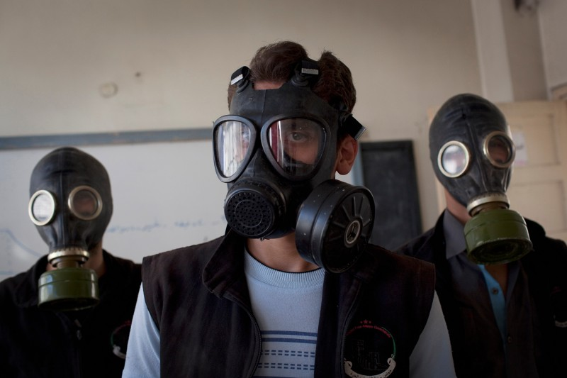 TO GO WITH AFP STORY BY ANTONIO PAMPLIEGA Volunteers wear gas masks during a class on how to respond to a chemical attack, in the northern Syrian city of Aleppo on September 15, 2013. For two months, Mohammad Zayed, an Aleppo University student, has been training a group of 26 civilians in the hope they can respond to a chemical attack.  AFP PHOTO / JM LOPEZ        (Photo credit should read JM LOPEZ/AFP/Getty Images)