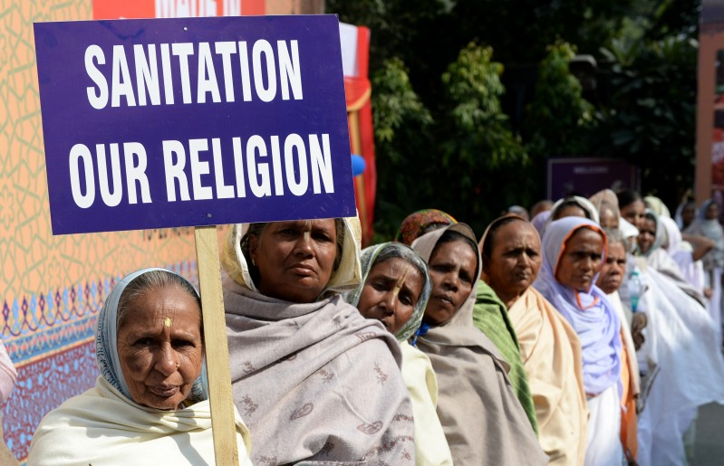An Indian woman holds a placard as others look on during a function to mark World Toilet Day In New Delhi on November 19, 2013. According to a 2011 census, some 131 million households in India have no latrine in their premises, with eight million using public facilities and 123 million defecating in the open. AFP PHOTO/SAJJAD HUSSAIN        (Photo credit should read SAJJAD HUSSAIN/AFP/Getty Images)